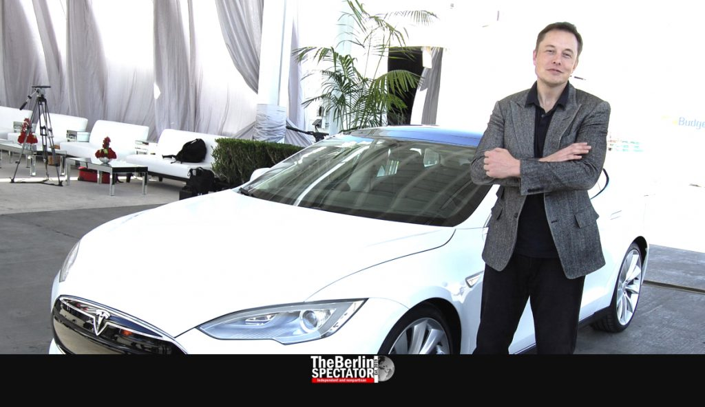 Elon Musk is standing in front of a Model S.